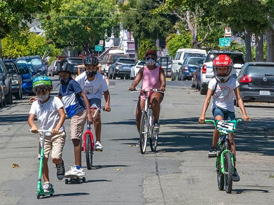 People riding bikes and scooters in a street