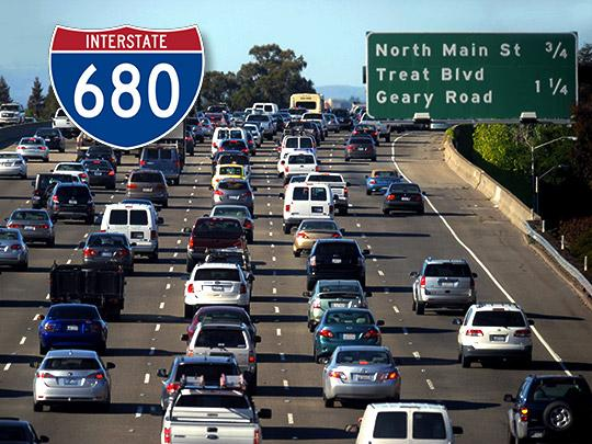 A packed freeway with the I-680 freeway sign overlayed on top