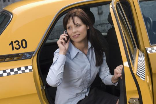 Woman on the phone entering a taxi