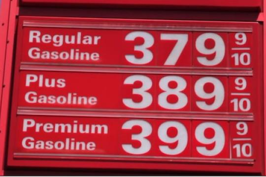 A red sign with gas prices