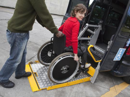 Woman in wheelchair being wheeled into van