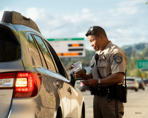 A CHP officer issuing a citation to a driver in vehicle pulled over from the I-680 Contra Costa express lanes.
